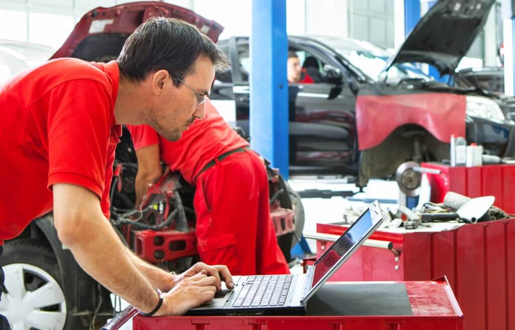 Group of mid aged male car mechanics at work performing regular maintenance. The closest mechanic is using laptop .Wearing red uniforms and standing within individual work spots. Blurry mechanics and cars in background.